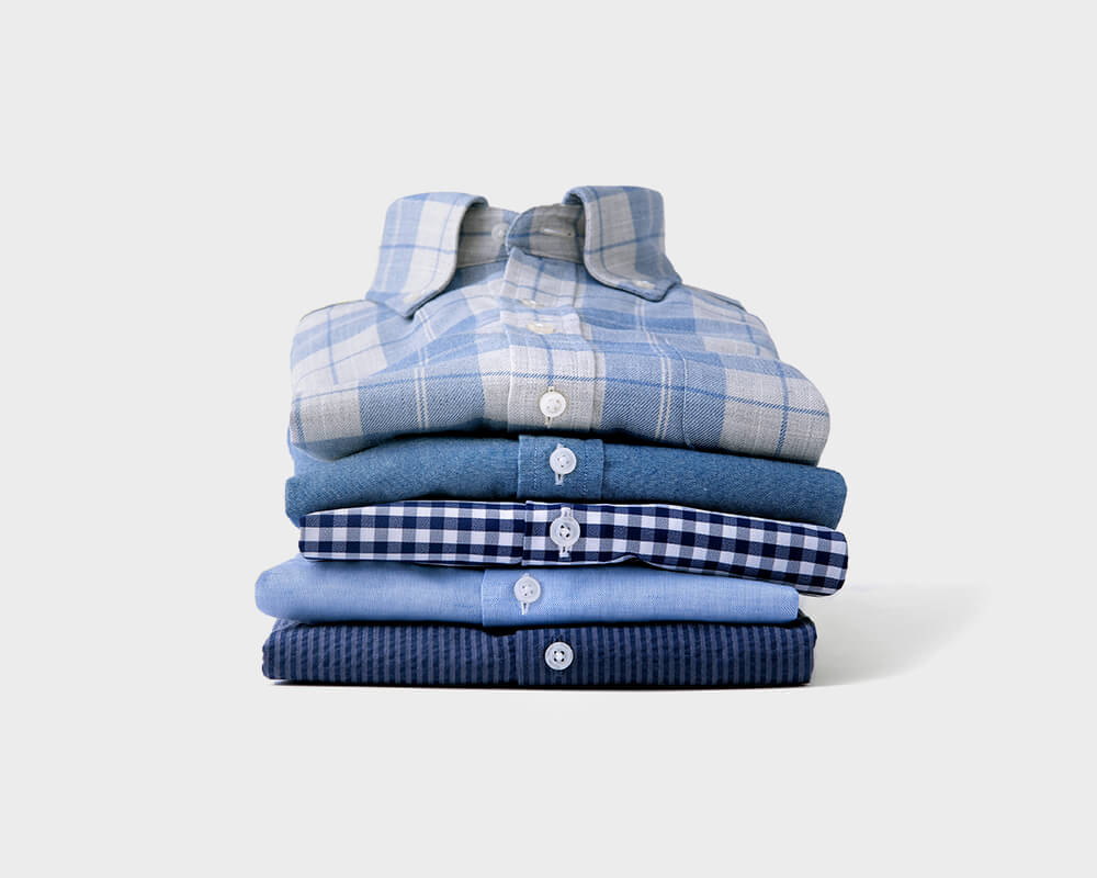 Custom Shirts of Various Colors and Patterns Stacked